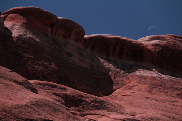 Moon above rock formation in Arches national park
