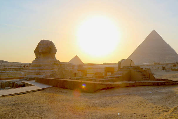 Sphinx at sunset and pyramids